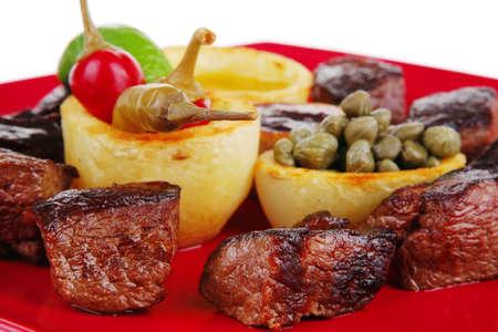 european food: europeo de alimentos: carne de res a la parrilla en plato de porcelana roja aislada en el fondo blanco con alcaparras y salsa de barbacoa Foto de archivo