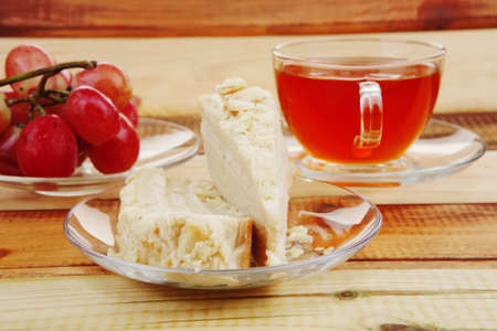grapes with tea and cake on wooden table photo