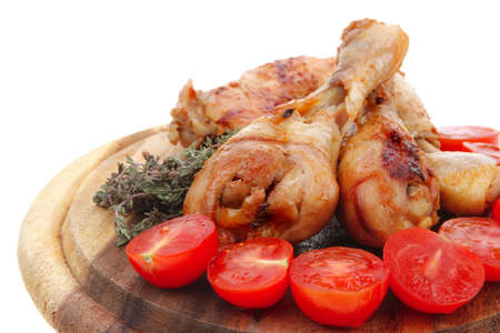 grilled chicken drumstick with tomatoes and thyme on wooden plate isolated over white background photo