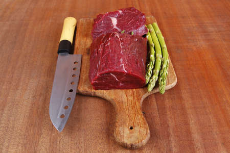 red fresh raw beef veal fillet with asparagus and stainless steel chef knife on cutting plate over wooden table prepared to use photo
