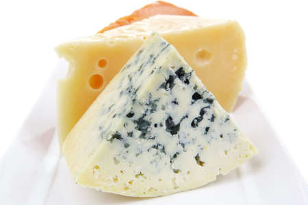 sustained: old blue stilton roquefort with orange cheddar and yellow parmesan on plate with isolated over white background Stock Photo