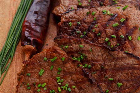 roasted beef meat fillet on wooden plate with thyme and chives isolated on white background photo