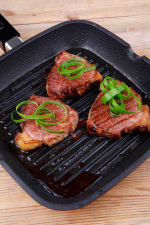 fresh grilled beef fillet strips on black grill plate over wood photo