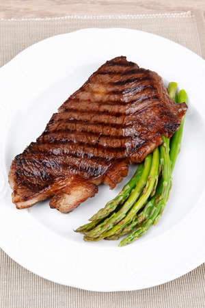 meat table : rare medium roast beef fillet with asparagus served on white plate with cutlery over wooden table photo