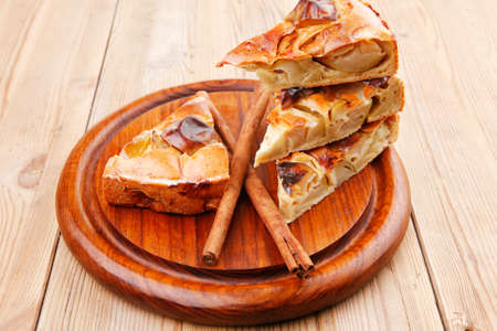 sweet food : cuts of apple pie on wooden plate over table with cinnamon sticks photo