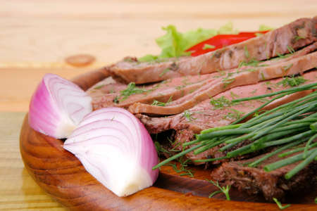 beef slices on wooden plate with peppers on wood photo