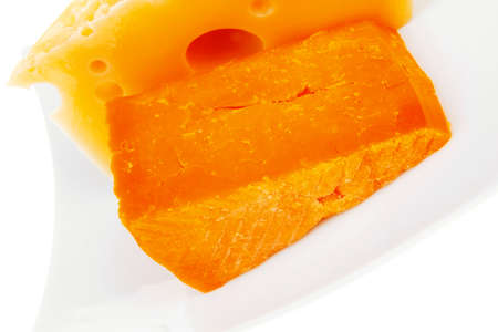 cheese : french gourmet triangles of yellow parmesan and orange cheddar on a plate isolated over white background Stock Photo - 22518412