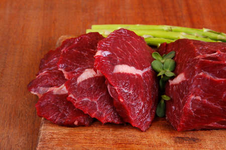 red fresh raw beef veal fillet with asparagus on cutting plate over wooden table prepared to use photo