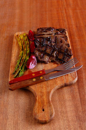 grilled beef pork meat steak fillet with asparagus  hot red peppers and cutlery on wooden cutting plate over wooden table photo