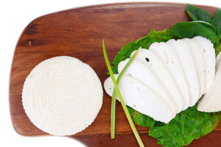 mediterranean cuisine : raw soft feta white cheese round with slices on wooden plate isolated over white background photo