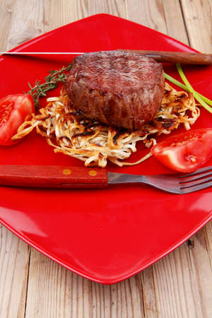 baby cutlery: grilled beef fillet medallions on noodles with red hot chili pepper on red plate over wood table