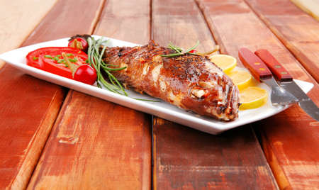 served main course on wood: whole fried seabass on plate with lemons,tomatoes and peppers photo