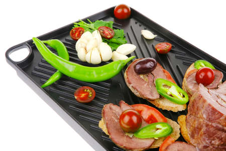 snakes on black teflon grill plate : meaty tartlets with supplements isolated over white background Stock Photo - 22903539