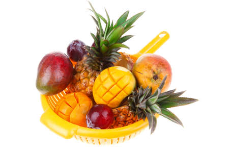 diet food - set of lot of tropical fruits include pineapple plum and mango in orange colander isolated over white background photo