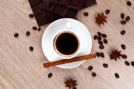 sweet hot drink : black Turkish coffee in small white mug with coffee beans spilled over a wooden table with stripes of dark chocolate and cinnamon stick photo