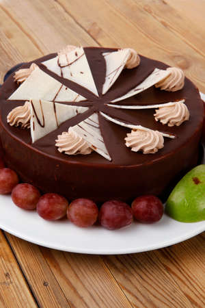 plum pudding: chocolate cream brownie cake topped with white chocolate slice and cream flowers decorated with fruits apple plum and grape on plate on wooden table