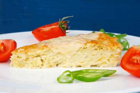 food : vegetable casserole triangle on white plate with pepper and tomatoes on blue table photo