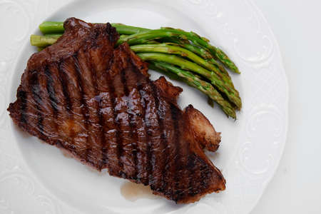 meat table : rare medium roast beef fillet asparagus served on white plate  isolated over white photo