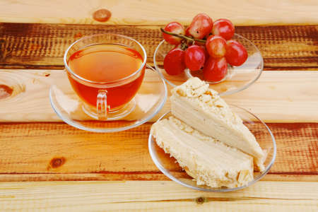 cream cake with tea and grapes on wood photo