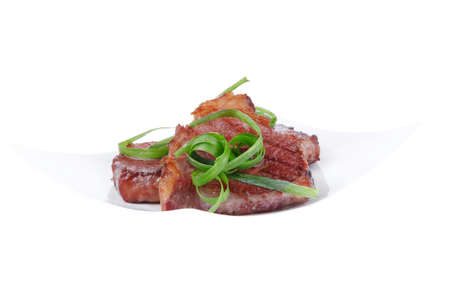 roasted beef meat strips steak on white ceramic plate isolated over white background photo