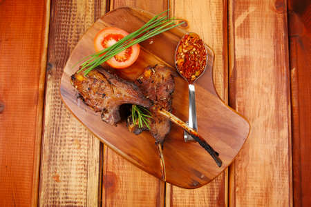 meat over wood: grilled ribs on plate with tomatoes and spices on wooden table photo