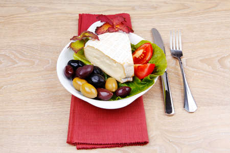aged camembert cheese on green salad in white dish over cloth with olives and over wooden table photo