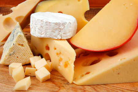 image of cheeses on wooden plate over table