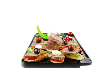 snacks on black grill plate : tartlets with sliced meat isolated over white background photo