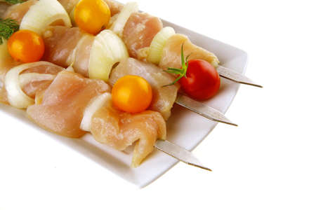 fresh chicken shish kebab on long white plate photo