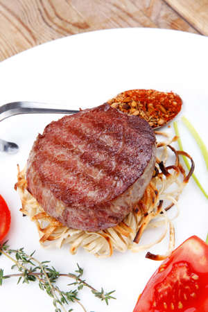 grilled beef fillet medallions on noodles with tomatoes and thyme twigs on white plate over wood photo