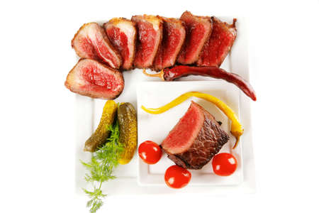 beef slices and vegetables on white plates photo