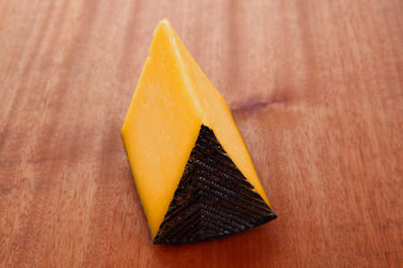 chunk of aged french gruyere or cheddar cheese in black shell on wooden table photo