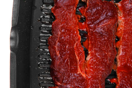 fresh raw bloody beef steaks on black grill plate isolated on white background photo