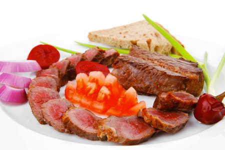 carne roja: plato: rodajas asadas de carne roja sirvi� en plato blanco con tomates, coles y pan aislados sobre fondo blanco Foto de archivo