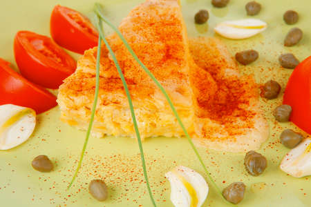 food : cheese casserole piece on green plate served with capers and tomatoes isolated over white photo