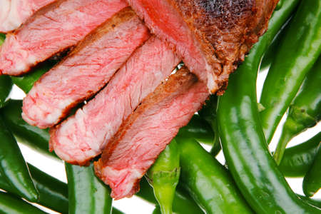 steak beef: meaty food : roast meat steak sliced over green hot chili peppers on a white background