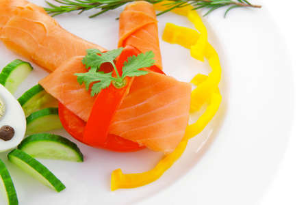 smoked salmon slices with vegetabls over white plate photo