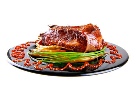 bloc: roast red beef meat bbq bloc served on black plate  with green chives adn red hot pepper on black plate isolated over white background