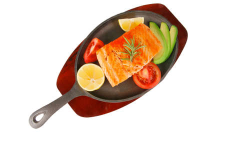 healthy diet food: hot sea grilled  red salmon fish fillet with lemon avocado and tomatoes on metal pan over wooden plate isolated on white background photo