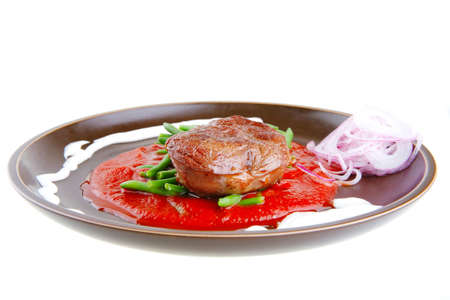 pork medallion served on tomato sauce with green peas on dark plate isolated on white background photo