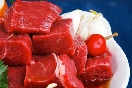 beef meat: slices of raw fresh beef meat fillet in a white bowls with garlic and red peppers serving on blue table with cutlery