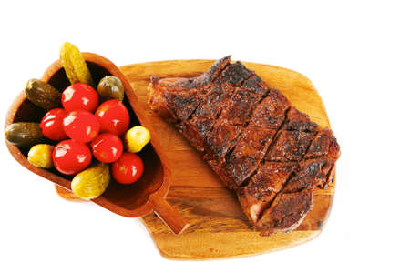 grilled steak entrecote and vegetables on wooden plate isolated over white background photo