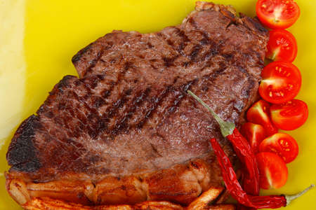 meat food : big grill beef meat steak on green square plate with dry hot chili pepper and cherry tomato isolated on white background photo
