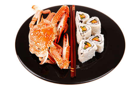philadelphia roll: Roll with Cucumber , Cream Cheese with raw Tuna and Salmon inside. on black dish with boiled crab . Japanese traditional Cuisine Stock Photo