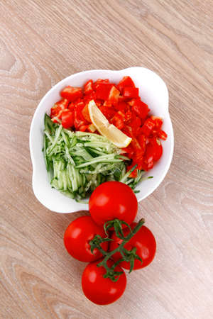 whole tomatoes on branch with salad of shredded tomatoes and cucumbers on white dish over wood table photo