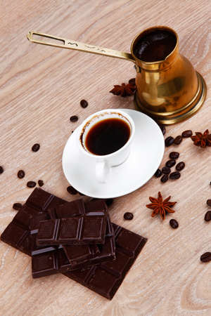 cezve: sweet hot drink : black coffee in small white cup with beans on a wooden table with stripes of dark chocolate and copper cezve Stock Photo