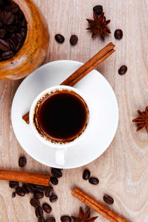 sweet hot drink : black arabic coffee in small white cup with mortar and pestle , beans spilled over wooden table , decorated with cinnamon sticks and anise stars photo