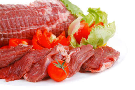 beef meat: raw meat on white plate with vegetables