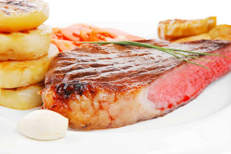 meat food : roasted fillet on white plate with tomatoes and chives isolated over white  photo