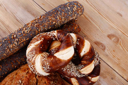 fresh rural homemade rye bread and baguette topped with sunflower seeds and sweet bagels on wooden tables photo